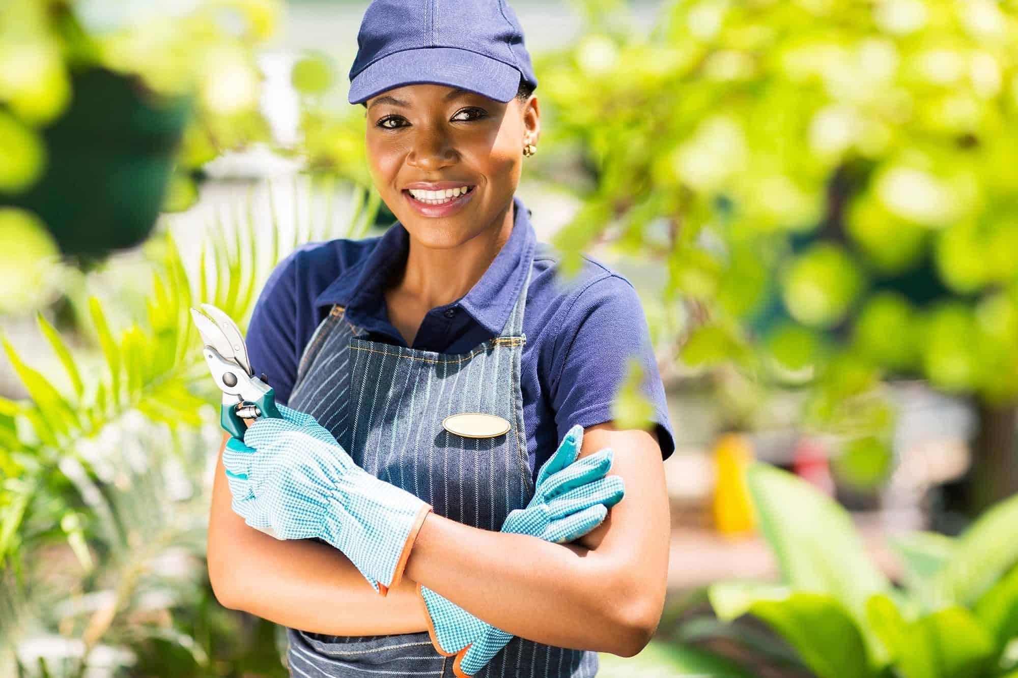 happy african nursery worker holding garden tool